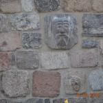 Ciosy kamienne przywiezione z Kurnika k. Poznania na powrót wmurowane w ścianę romańskiej bazyliki.
